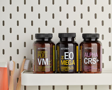 doTERRA Microplex VMz, xEO Mega and Alpha CRS+ on a bathroom shelf with bathroom accessories.