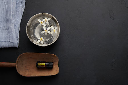 doTERRA Cheer in a wooden scoop with orange blosson flowers in a bowl of water on a black concrete backgrouns.
