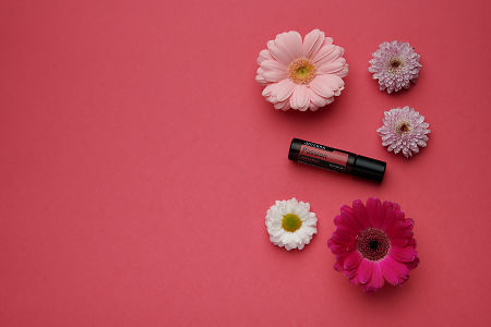 doTERRA Passion Touch with flowers on a dark pink card stock background.