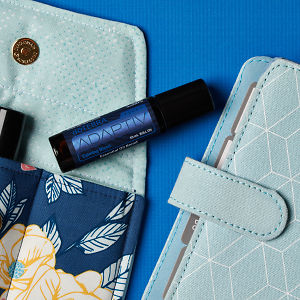doTERRA Adaptive Touch on an essential oil bag with a diary on a blue textured background.