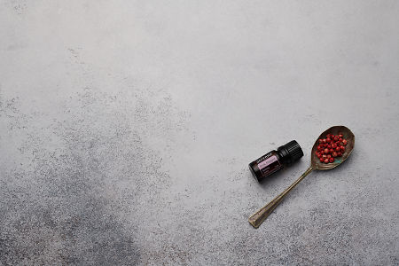 doTERRA Pink Pepper and pink peppercorns in a vintage spoon on a white concrete background.