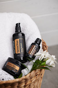 doTERRA Yarrow Pom, Body Renewal Serum and Cellular Beauty Capsules on a white towel in a cane basket.