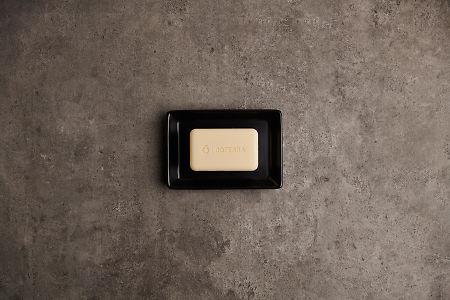 doTERRA Spa Moisturizing Bath Bar in a black soap dish on a gray stone bathroom bench.