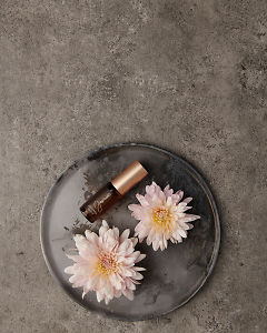 doTERRA Jasmine Touch 4ml on a ceramic plate with flowers on a gray stone background.