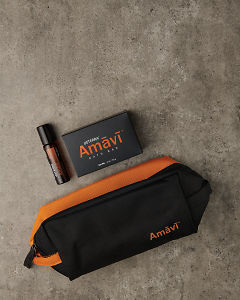 doTERRA Amavi Touch, Amavi Bath Bar and an Amavi bathroom bag on a gray stone background.