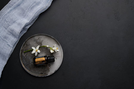 doTERRA Citrus Bliss with orange blossom flowers on a ceramic plate on a black concrete baclground.