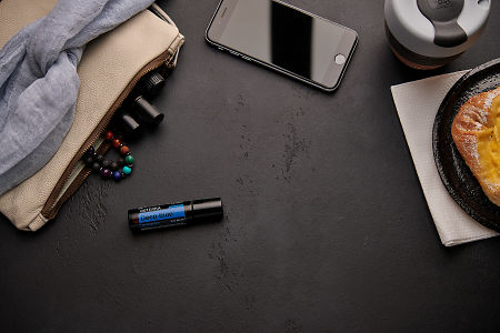 doTERRA Deep Blue Touch with a leather clutch, roller bottles, cell phone, coffee and food on a black background.