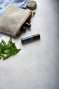 doTERRA Deep Blue Touch with clutch, accessories and mint leaves on a white concrete background.