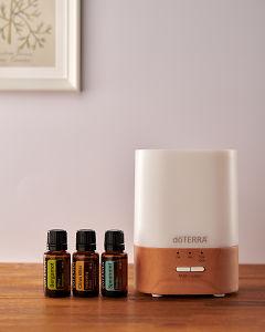 doTERRA Lumo diffuser with Bergamot, Citrus Bliss and Spearmint essential oils on a side table.