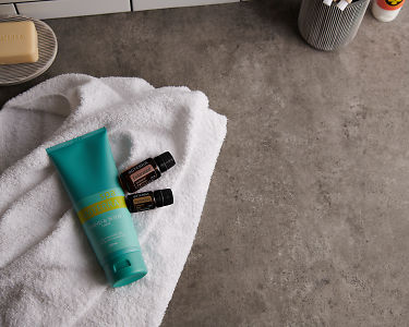 doTERRA Spa Hand and Body Lotion with Cedarwood and Sandalwood essential oils and bathroom accessories  on a white towel on a stone background.