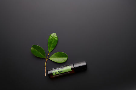doTERRA Forgive Touch with leaves on a black background.