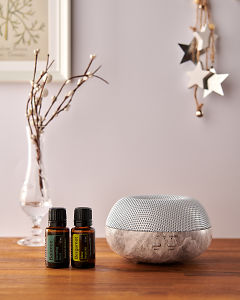 doTERRA Brevi Stone diffuser with Balance and Bergamot essential oils and holiday decorations on a side table.