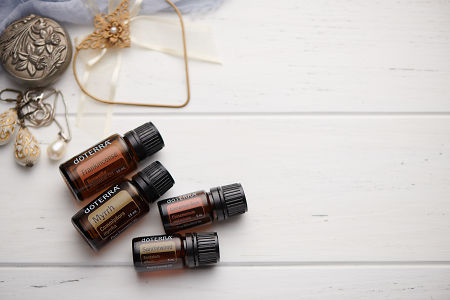 doTERRA Frankincense, Myrrh, Cinnamon and Sandalwood oils with romantic jewellery on a white vintage wooden background.