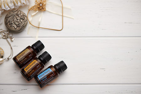 doTERRA Ginger, Wild Orange and Ylang Ylang oils and wedding accessories on white rustic wooden background.
