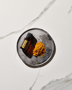 doTERRA Turmeric essential oil and ground turmeric on a small ceramic plate on a marble background in  sunlight.