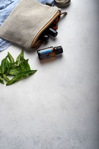 doTERRA Breathe with clutch, accessories and mint leaves on a white concrete background.