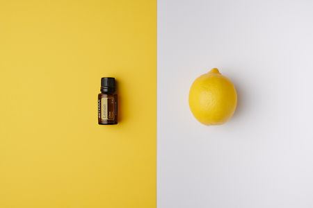 doTERRA Lemon oil on yellow background and whole lemon on white background.
