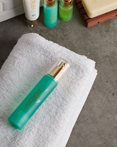 doTERRA Verage Toner with a white fluffy towel on a stone bathroom bench top.