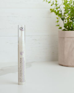 doTERRA Essential Skin Care Anti-Ageing Eye Cream sitting on a white bench near a pot plant.