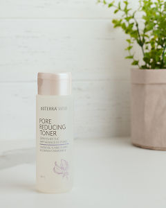 doTERRA Essential Skin Care Pore Reducing Toner sitting on a white bench near a pot plant.