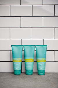 Three doTERRA Spa Hand and Body Lotions on a gray stone bathroom benchtop.