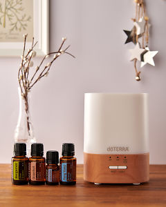 doTERRA Lumo diffuser with Bergamot, Grapefruit, Juniper Berry and Ylang Ylang essential oils and holiday decorations on a side table.