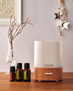 doTERRA Lumo diffuser with Passion, Bergamot and Lime essential oils and holiday decorations on a side table.