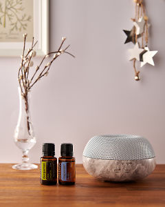 doTERRA Brevi Stone diffuser with Bergamot and Peppermint essential oils and holiday decorations on a side table.