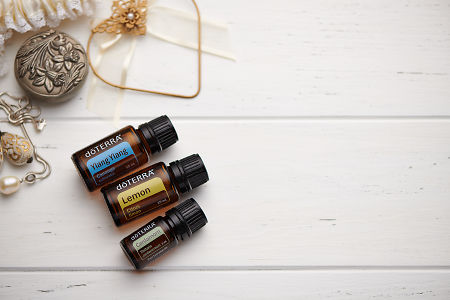 doTERRA Ylang Ylang, Lemon and Cardamom oils and wedding accessories on white rustic wooden background.