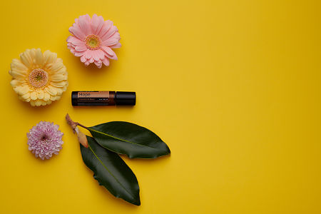 doTERRA Hope Touch with flowers and green leaves on a yellow card stock background.