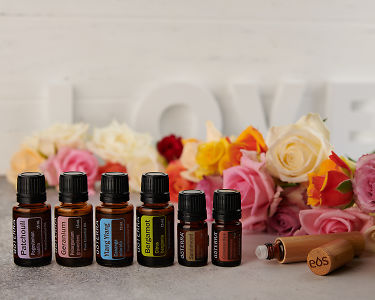 doTERRA Patchouli, Geranium, Ylang Ylang, Bergamot, Sandalwood and Cinnamon Bark with a bamboo roller bottle and roses on a concrete bench top.