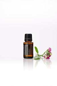 doTERRA Copaiba with flowers on a white background with reflection.