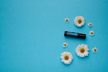 doTERRA Peace Touch with white flowers on a blue card stock background.