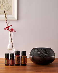 doTERRA Brevi Walnut diffuser with Cardamom, Cinnamon, Clove and Wild Orange essential oils on a side table.
