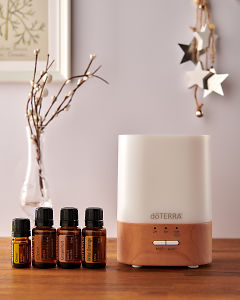 doTERRA Lumo diffuser with Cheer, Clove, Grapefruit and Wild Orange essential oils and holiday decorations on a side table.
