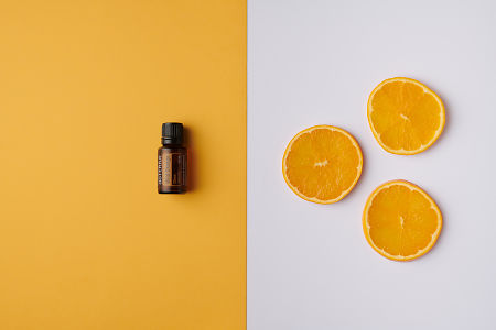 doTERRA Wild Orange oil on orange background and orange  slices on white background.