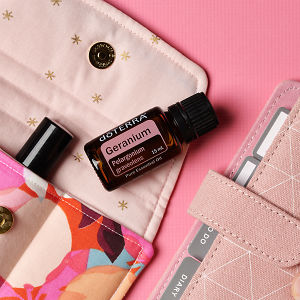doTERRA Geranium on an essential oil bag with a pink diary on a pink textured background.