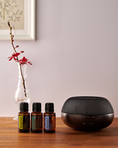 doTERRA Brevi Walnut diffuser with Bergamot, Cypress and Peppermint essential oils on a side table.