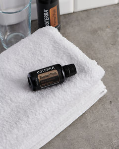 doTERRA Yarrow Pom on a white towel on a gray stone bathroom bench top.