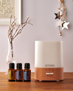 doTERRA Lumo diffuser with Lemon, Peppermint and Ylang Ylang essential oils and holiday decorations on a side table.