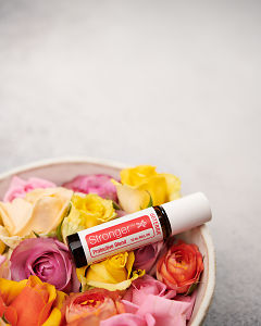 doTERRA Stronger in a bowl of roses on a white background.