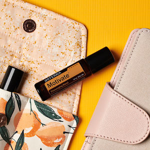doTERRA Motivate Touch on an essential oil bag with a pink diary on a yellow textured background.