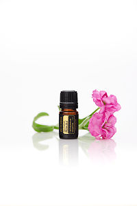 doTERRA Manuka with flowers on a white background with reflection.