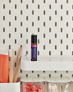 doTERRA Clary Calm on a bathroom shelf with additional doTERRA products and bathroom accessories.
