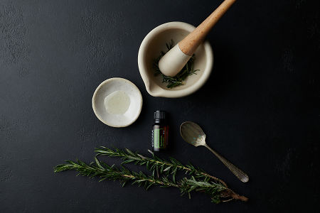 doTERRA Rosemary with a mortar and petsle, a vintage spoon, a rustic bowl and a rosemary branch on a black stone background.