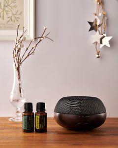 doTERRA Brevi Walnut diffuser with Balance and Bergamot essential oils and holiday decorations on a side table.