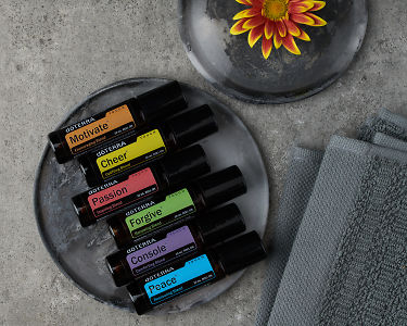 Close up of doTERRA Emotional Aromatherapy Touch Kit and a flower on gray ceramic plates on a gray stone background.