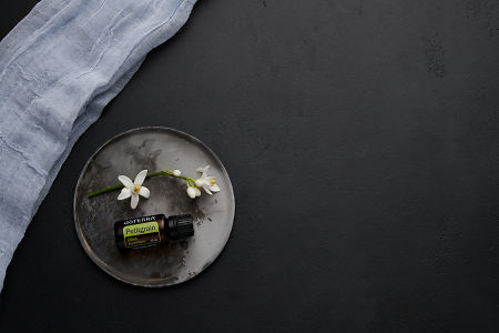 doTERRA Petitgrain with orange blossom flowers on a ceramic plate on a black concrete baclground.