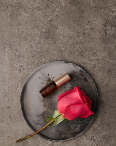 doTERRA Rose Touch 4ml on a ceramic plate with a rose on a gray stone background.
