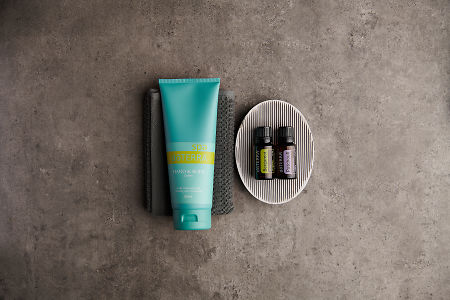 doTERRA Spa Hand and Body Lotion with Bergamot and Patchouli essential oils with bathroom accessories on a stone background.